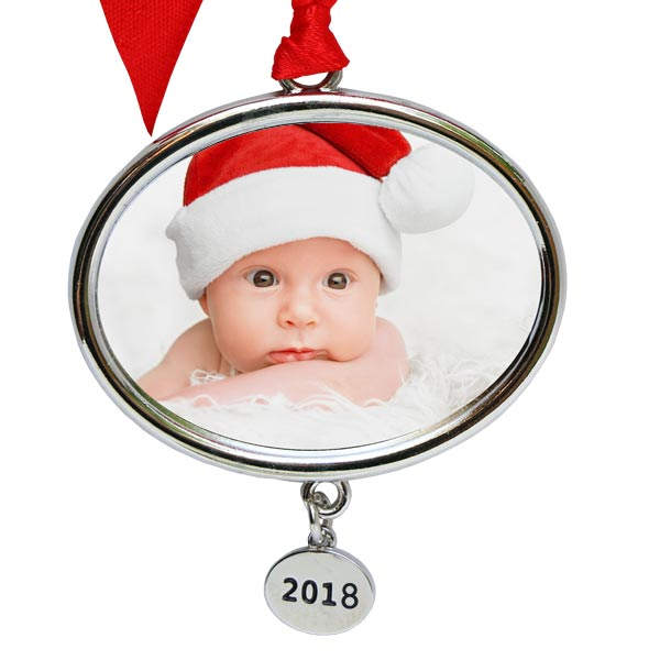 Silver oval ornament with large ribbon tie and pendant that displays the current year